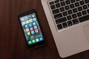 black iphone 4 beside macbook pro