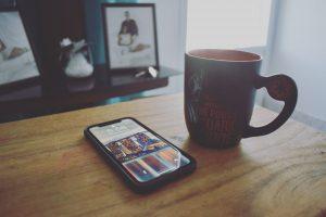 black iphone 5 beside black ceramic mug on brown wooden table